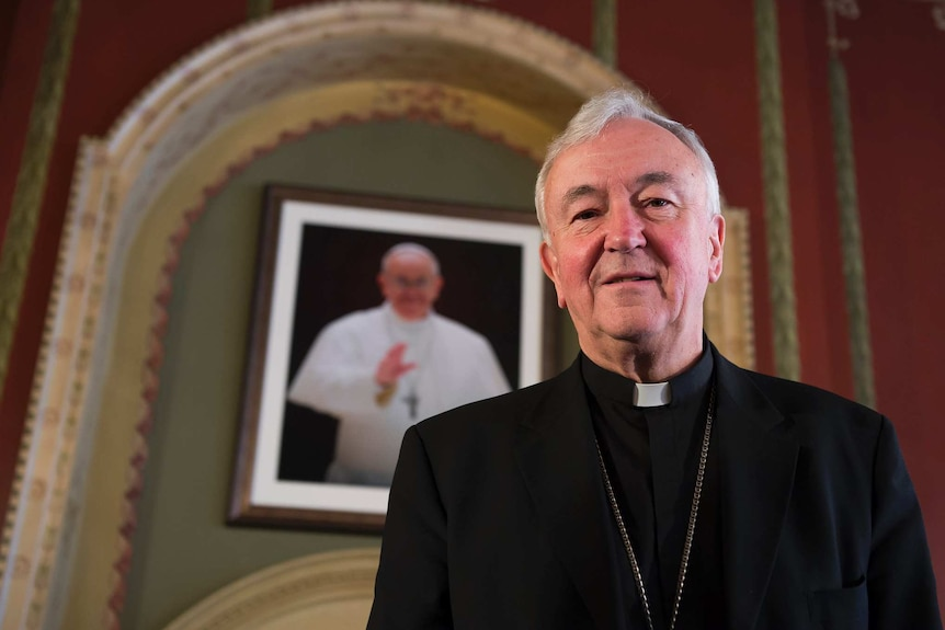 You view Vincent Nichols in a black suit with a priest's white collar standing in front of a portrait of Pope Francis.