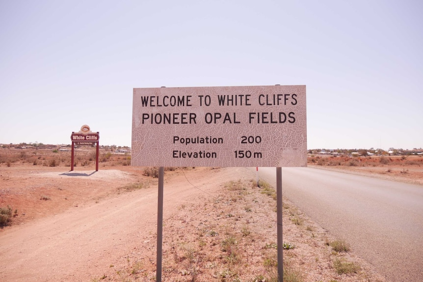 A sign reading 'Welcome to White Cliffs - Pioneer Opal Fields' by the side of a road.