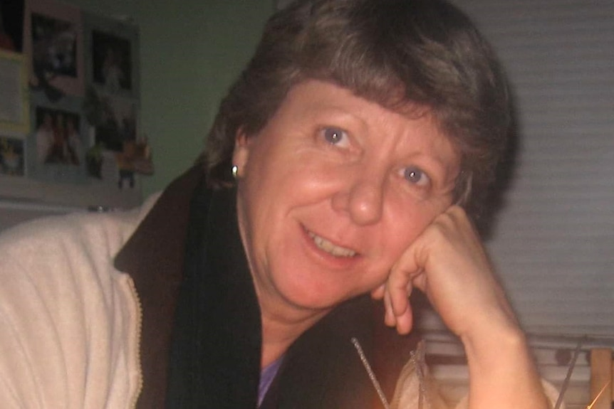 A head and shoulders shot of Dianne Barrett posing for a photo with her head resting on a hand.