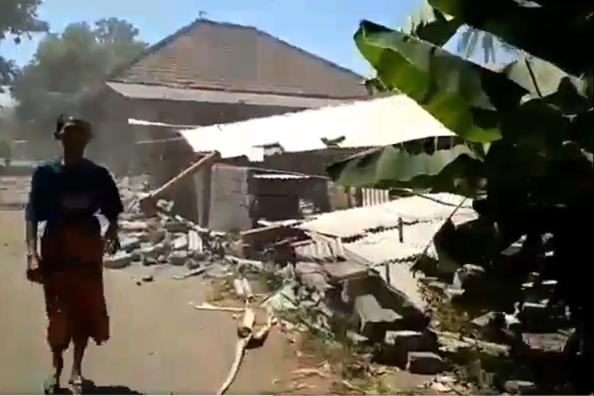 A man runs amid damaged buildings