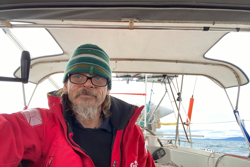Self of man in red coat, glasses and green beanie at helm of boat at sea