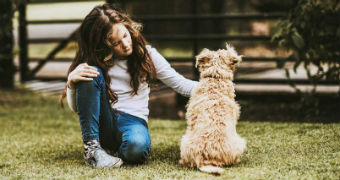 A girl sits on the lawn next to her dog