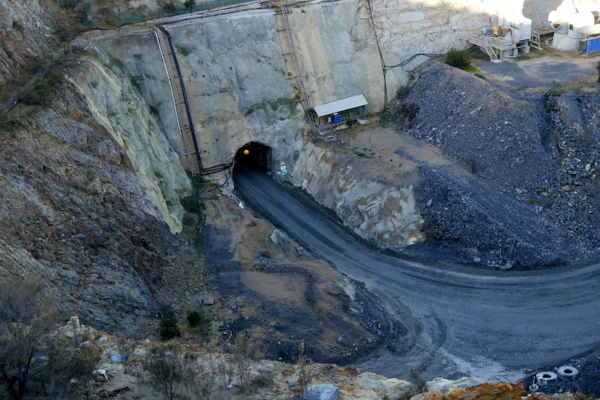 A road leads into the mouth of a cave cut into the side of the open cut mine