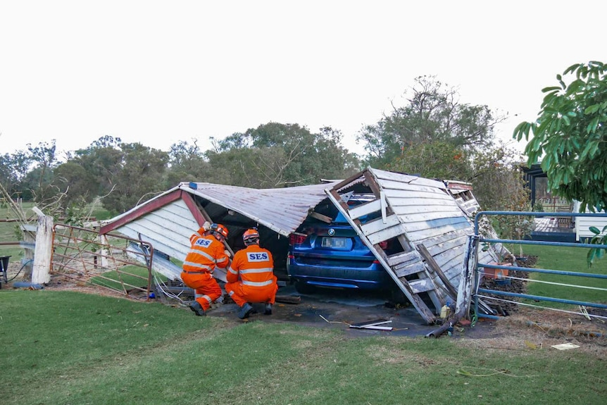 Two men in orange SES suits inspect a collapsed garage over a blue car.