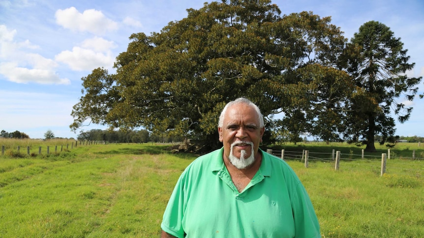 Uncle Richard Campbell stands in front of a large tree, smiling.
