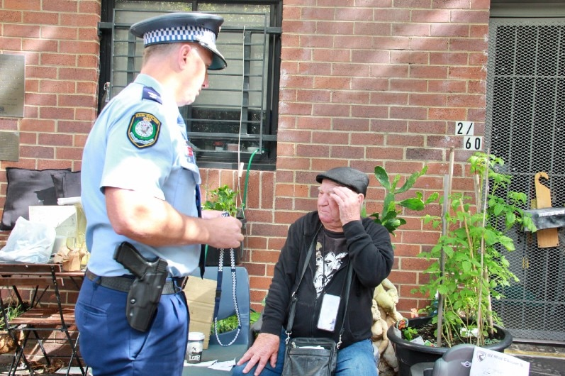 A police officer with an elderly man who is sitting down.