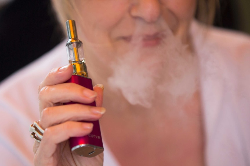 A woman holding an e-cigarette blows smoke through her nostrils.