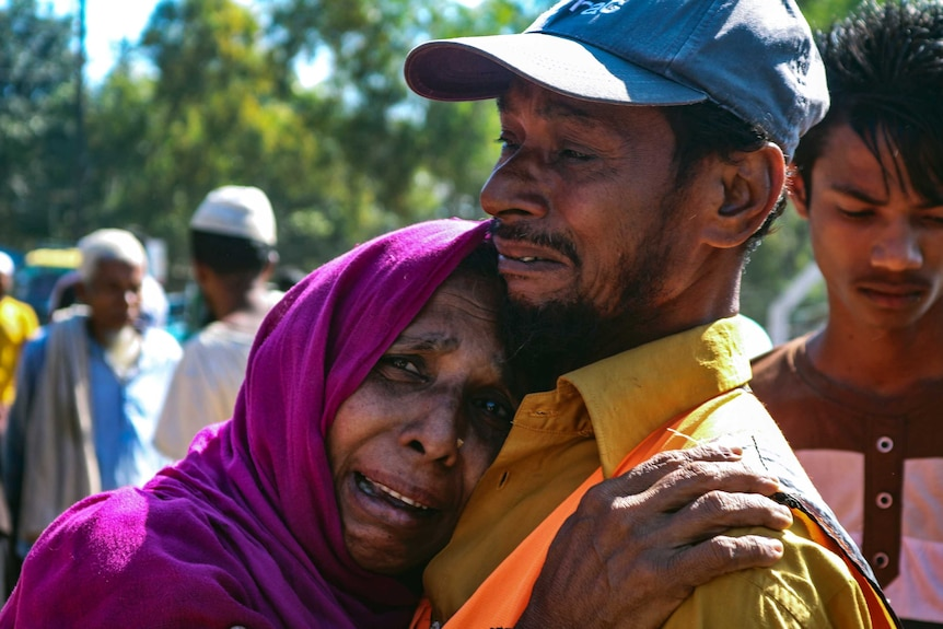A woman in tears hugs a man, who is also crying.