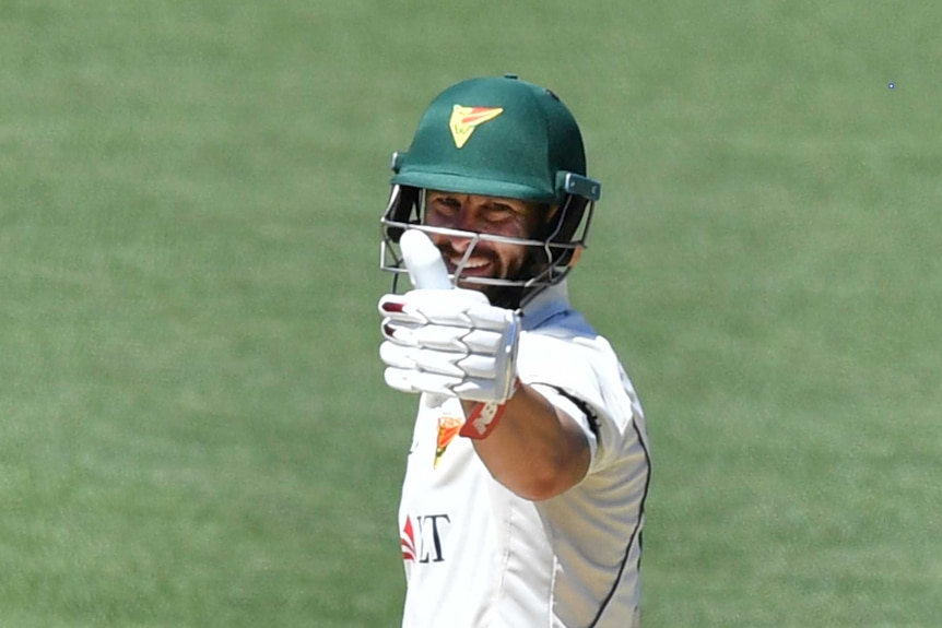 Matthew Wade holds his gloved thumb up with a smile on his face