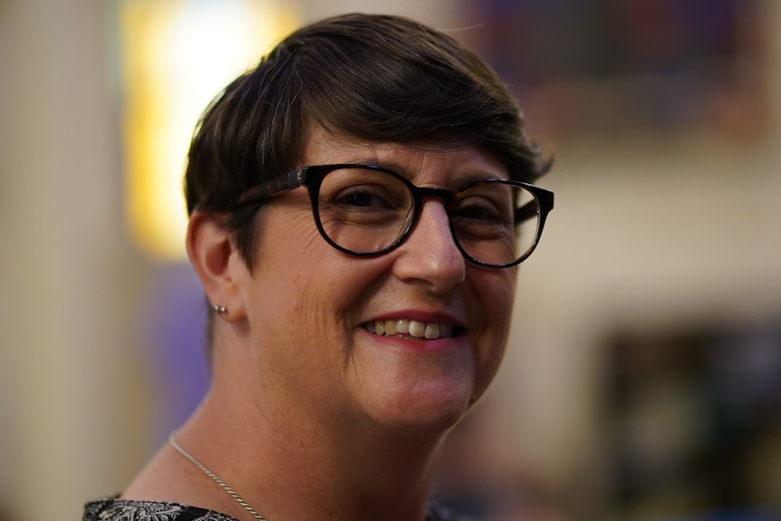 Woman with short hair and black-framed glasses smiling.