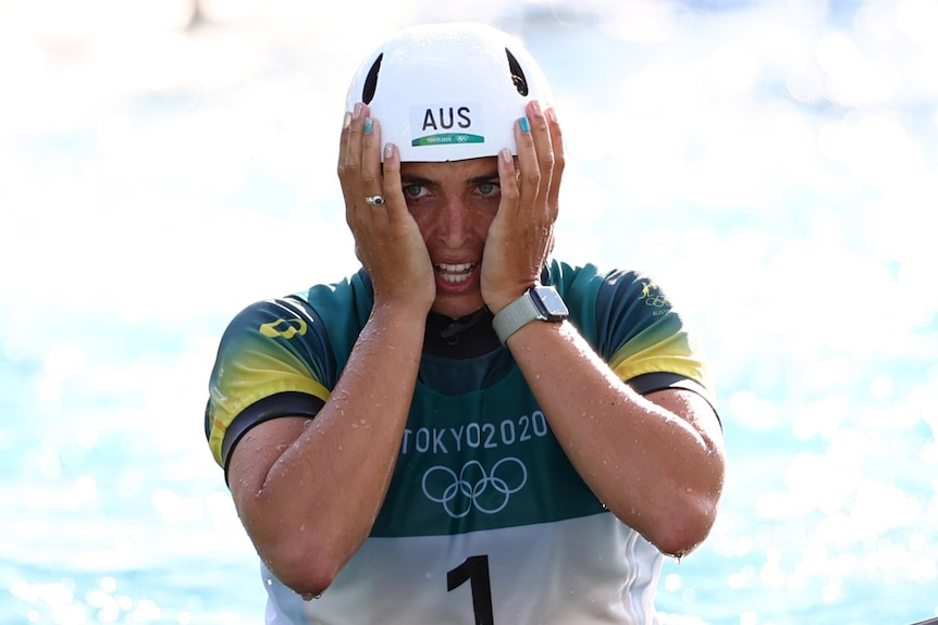 An Australian female kayaker holds her face between her two hands after placing third at the Tokyo Olympics.