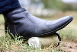 A disposable coffee cup is crushed by a foot.
