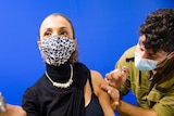 A woman in a leopard face mask receives an injection in her shoulder