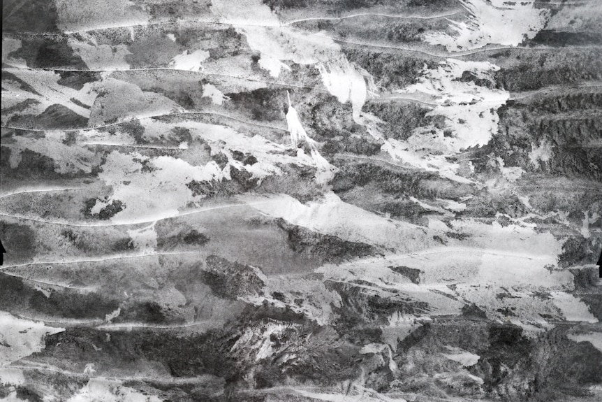 A black and white aerial image of sand dunes and fire scars.