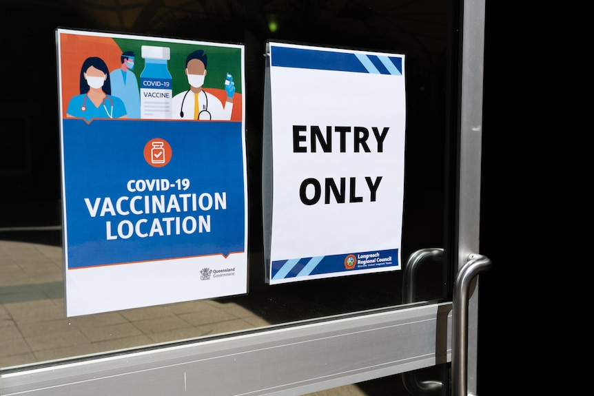 """Two signs on a door that say """"COVID-19 vaccination location"""" and """"entry only""""."""