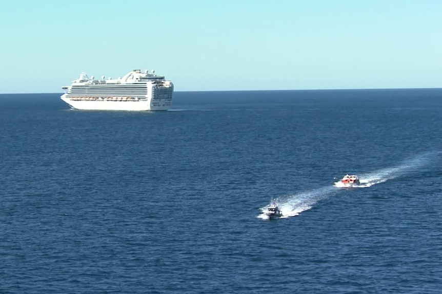 Two much smaller boats move across the water away from a large cruise ship.
