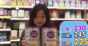 An Asian-looking woman holding cans of baby formula in front of an Australian supermarket shelf with Chinese writing overlaid.
