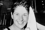 An Australian female swimmer dries her hair after a swim and smiles in 1960.