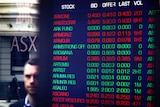 A man's face is reflected in the window of the Australian Securities Exchange. Inside a board is lit with various falling stocks