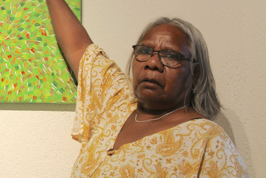 An Indigenous woman pointing at a painting.