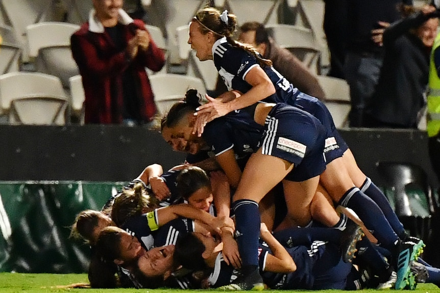 Melbourne Victory W-League players embrace as they celebrate the winning goal in the grand final.