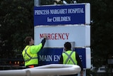 Two men in hi-vis clothing take down an emergency department decal on a Princess Margaret Hospital sign.