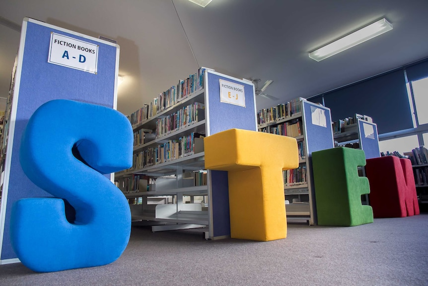 Big fabric letters in blue, yellow, green and red spelling STEM in front of aisle of a school library