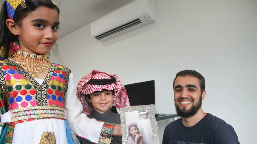 Two Muslim children with their father