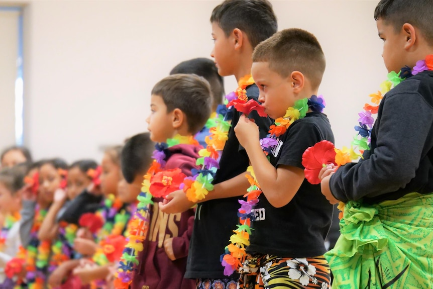 Young children with colourful lei's around their neck wearing traditional sarongs