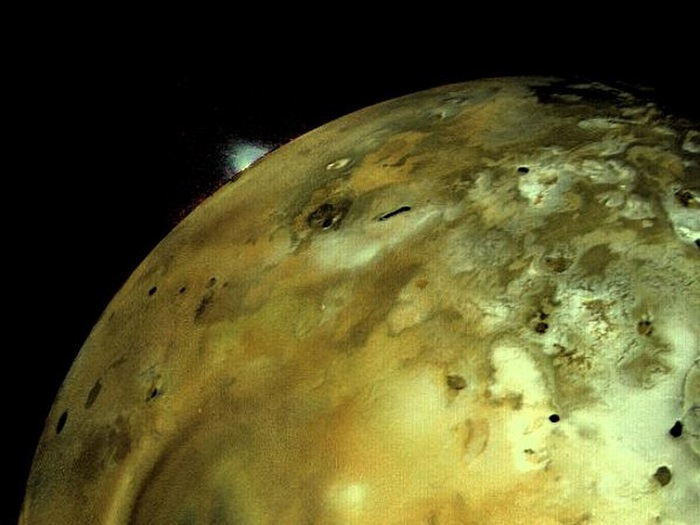 A close-up view of the surface of Jupiter's moon, Io, which is an odd brown-green in colour