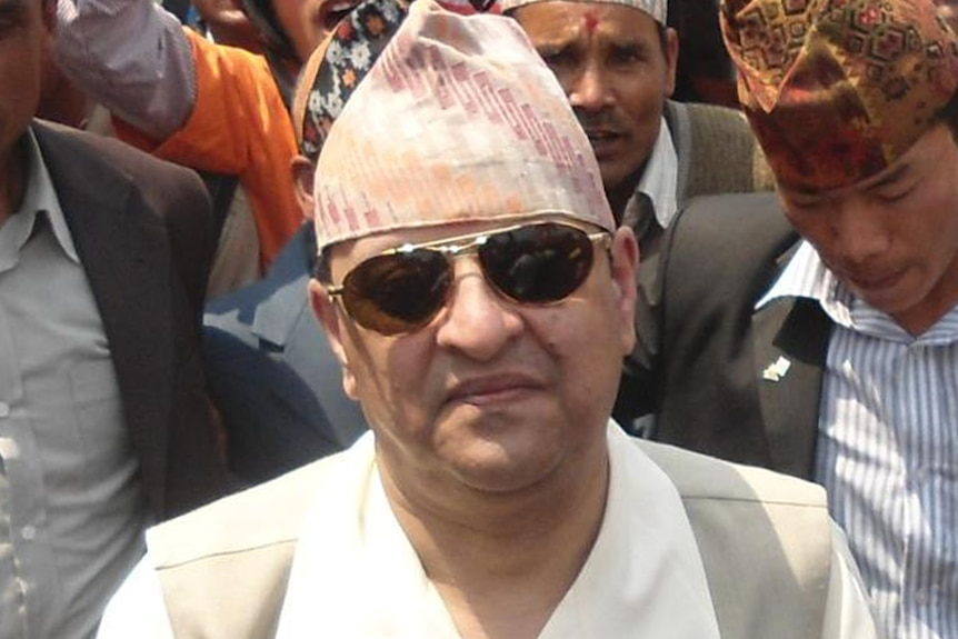 King Gyanendra in a white shirt, cream vest and traditional Dhaka topi hat