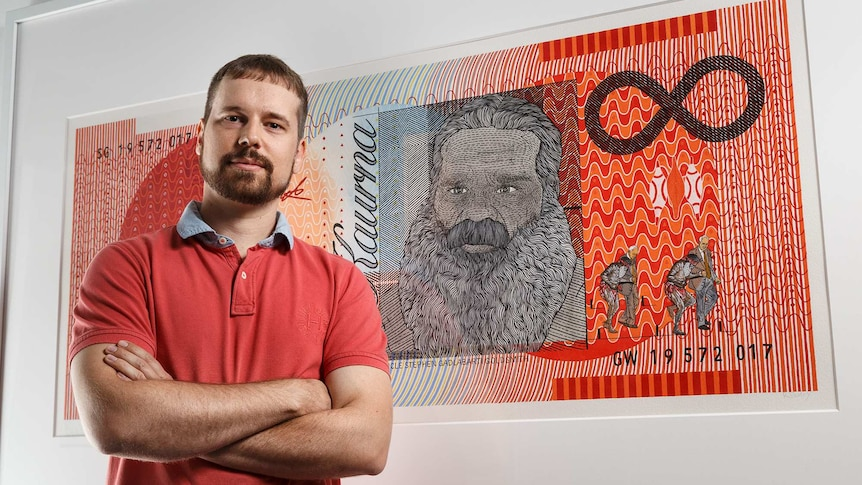 presley in a red shirt, arms crossed in front of his painting of the orange $20 note.