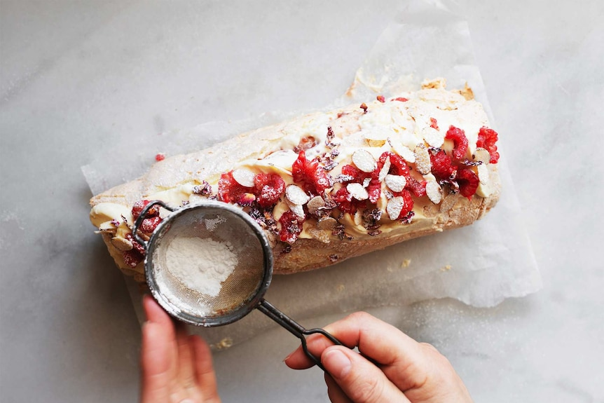 Dusting icing sugar over a pavlova roll topped with cream, raspberries and almonds for a festive dessert.