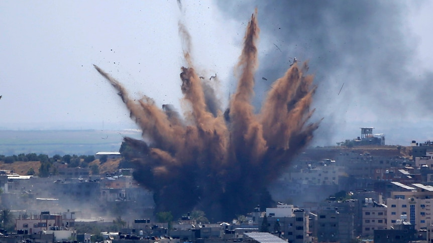 A large cloud of smoke rises following an airstrikes on a building in Gaza City