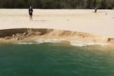 People stand near landslip into the sea at Inskip Point on Queensland's Cooloola Coast.
