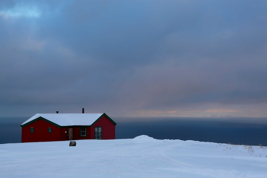 A house overlooks the ocean on the isolated archipelago of Svalbard, deep in the Arctic Circle.