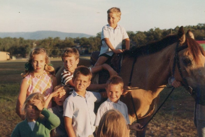 Children including young English migrant Paul Gilmore surround a horse.