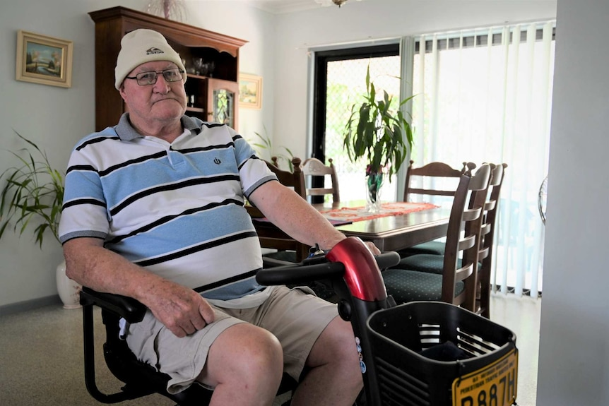 a man in a beanie sitting on an electric scooter