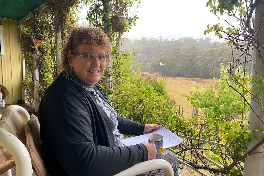 A woman sitting on a veranda overlooking farmland and bush, holding a cup of tea and a printed document.