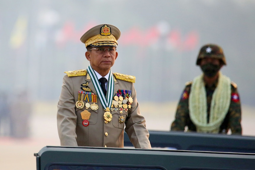 An elderly Asian man in decorative military uniform stands at a podium with a military parade behind him.