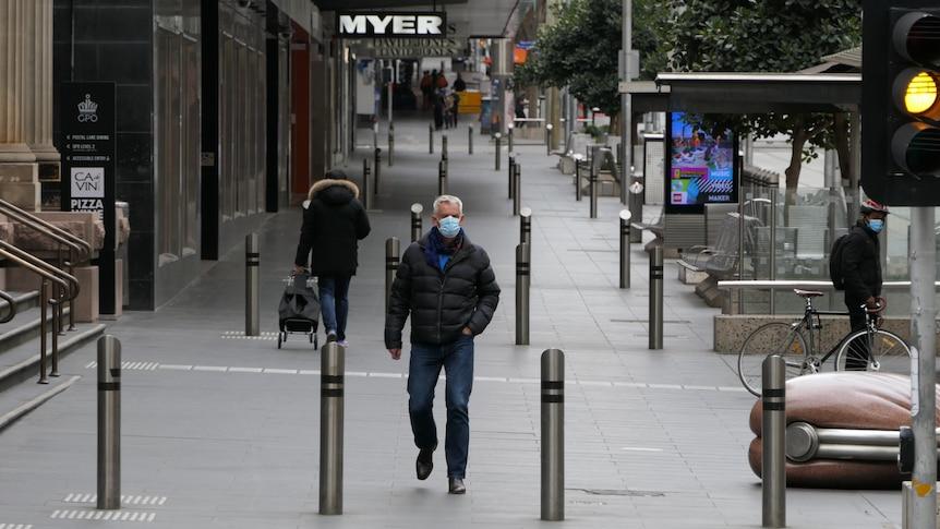 A man in a mask walks down an empty street.