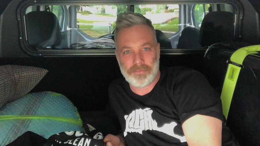 A man seated in the back of a van.