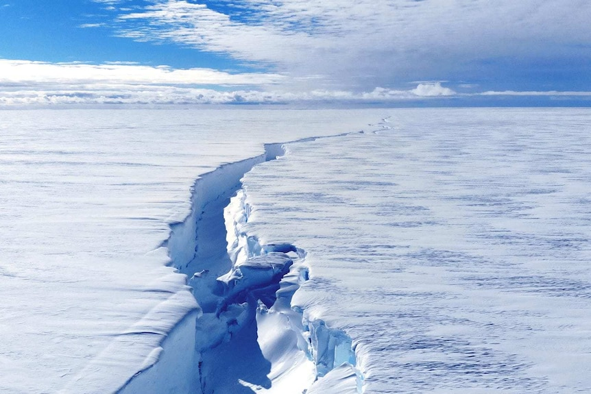 A huge crack emerges in a thick sheet of ice so large it stretches into the horizon.