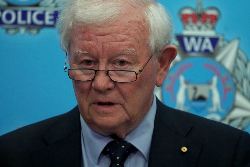 Mr Glennon stands in front of a wall covered in WA Police logos. He looks over the top of his glasses as he speaks.