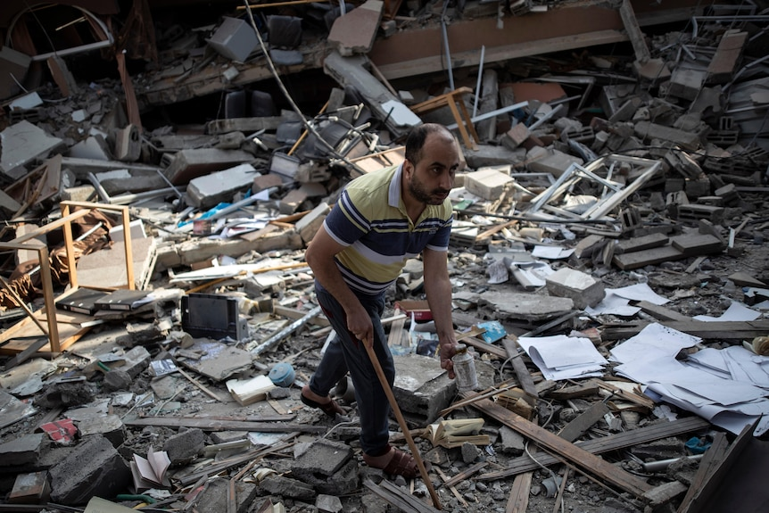 A Palestinian man inspects the damage of a house destroyed by an early morning Israeli airstrike in Gaza City