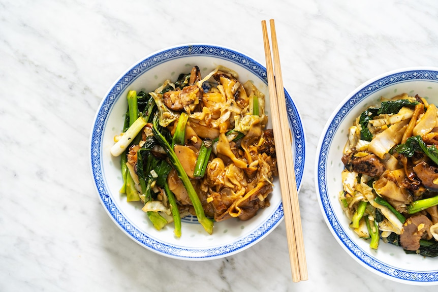 A bowl of thick rice noodles served with gravy and vegetables, a vegetarian family dinner by Hetty McKinnon.