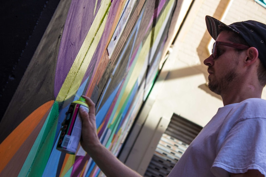 Adelaide artist Vans the Omega works in his mural in a laneway off King Street