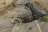 A section of highway buckled by a sinkhole.