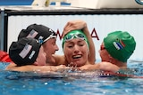A female swimmer cries tears of joy as three competitors hug and congratulate her in the pool.