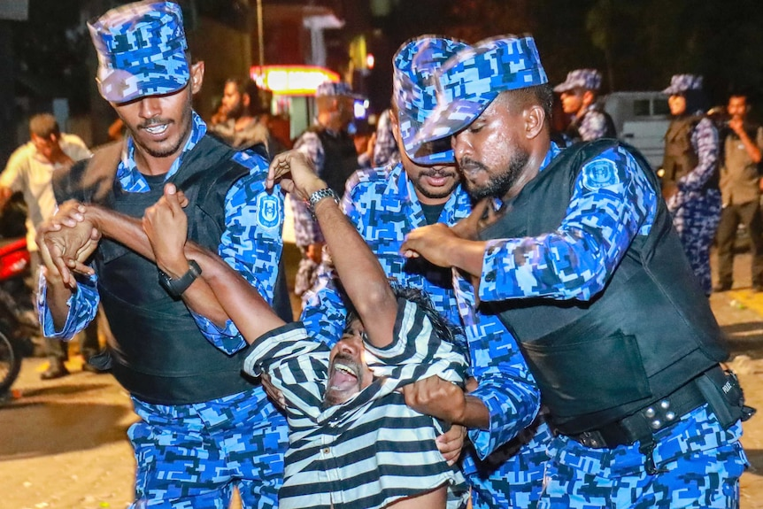 Three Maldivian police officers drag a protester away.